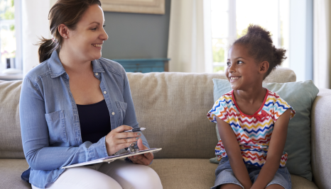 woman with a clipboard talking to a child on a couch