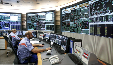 two men sitting in front of several large screens at a command center